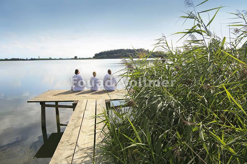 Drei sitzen im Bademantel am See