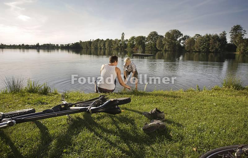 Radfahrer erfrischen sich am See