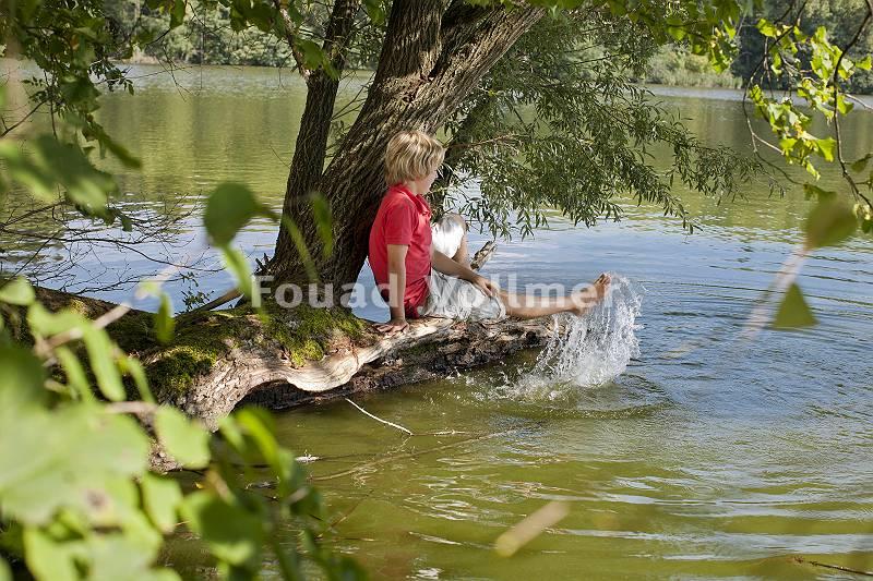 Planschender, spielender Junge am Gewässer