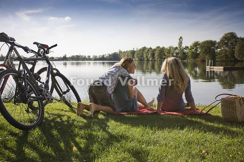Freundinnen rastet mit Sohn nach Radtour am Seeufer