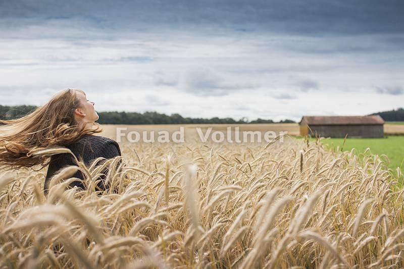 glückliche junge Frau mit langem wehendem Haar genießt den Win
