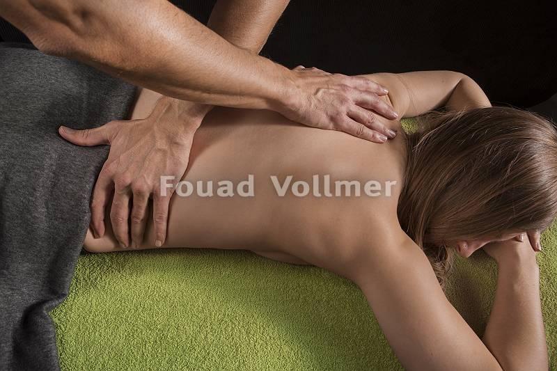 Masseur massiert den Rücken einer rothaarigen Frau