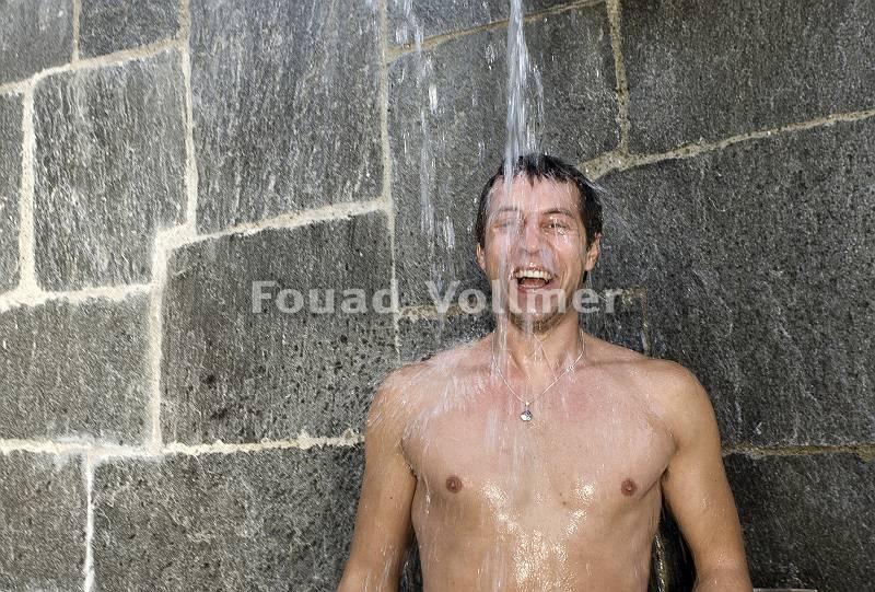 Abhärten unter der eisigen Dusche nach Saunagang