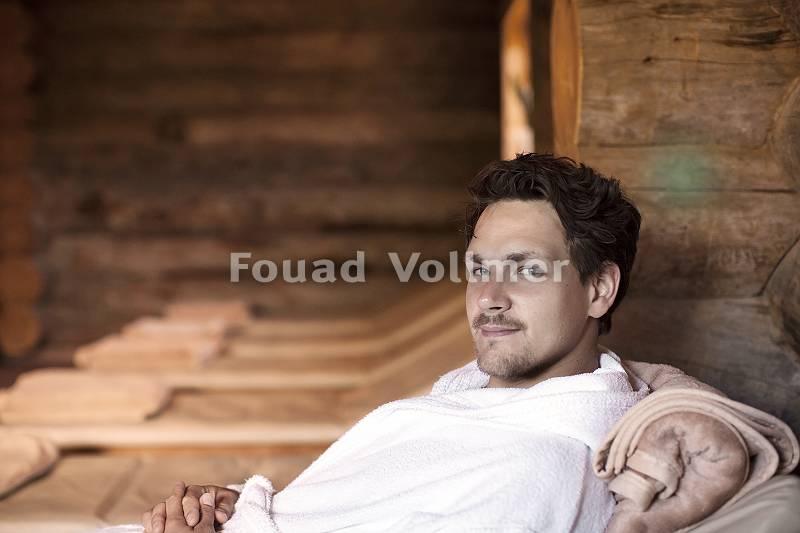 Mann im Bademantel auf einer Ruheliege