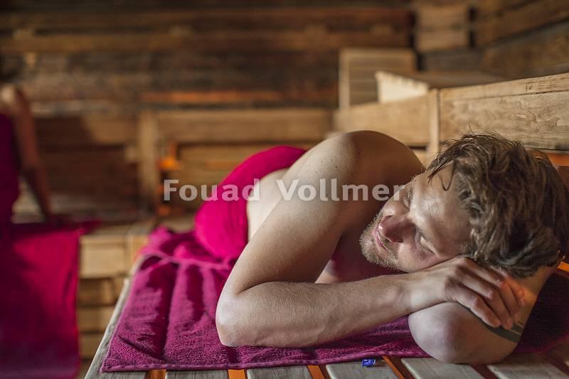 Mann auf Handtuch iliegend in der Sauna